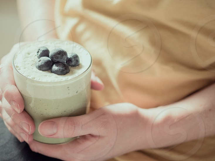 A woman holding a green tea smoothie with blueberries on top.  photo