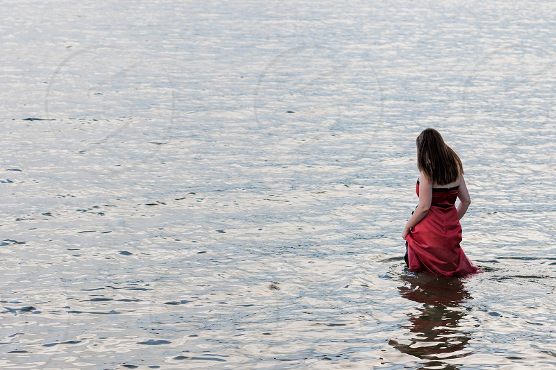 A woman in a red dress walking into a lake.  Release available upon request. photo