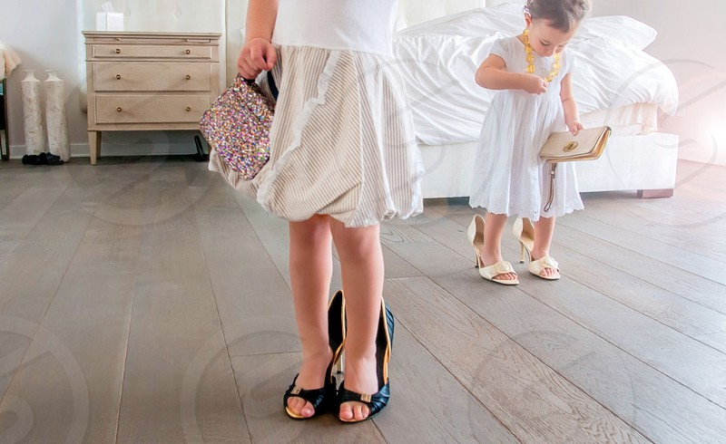 girl wearing white skirt trying on oversized dark blue high heels while another child plays with a book in the background photo