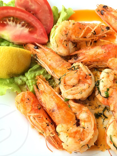 cooked shrimp beside sliced tomatoes photo