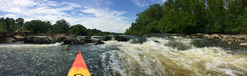 Panoramic shot of the front of a kayak facing the rapids it just emerged from. photo