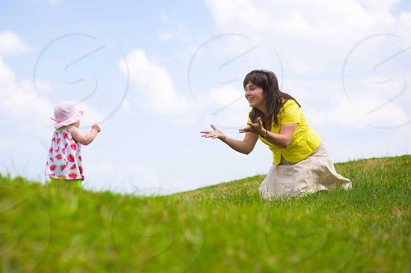 woman in yellow button up shirt kneeling on green grass calling for girl wearing pink bucket hat to walk towards her photo