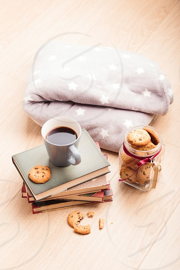 A few books with cup of coffee and cookies on wooden floor photo