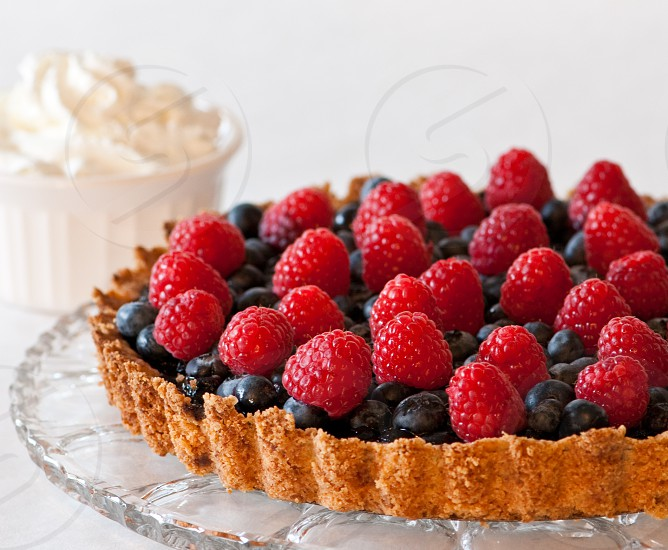 Blueberry raspberry tart with a crumb crust on a clear crystal serving plate on a white background with a whipped cream filled ramekin angled off to the side.   photo