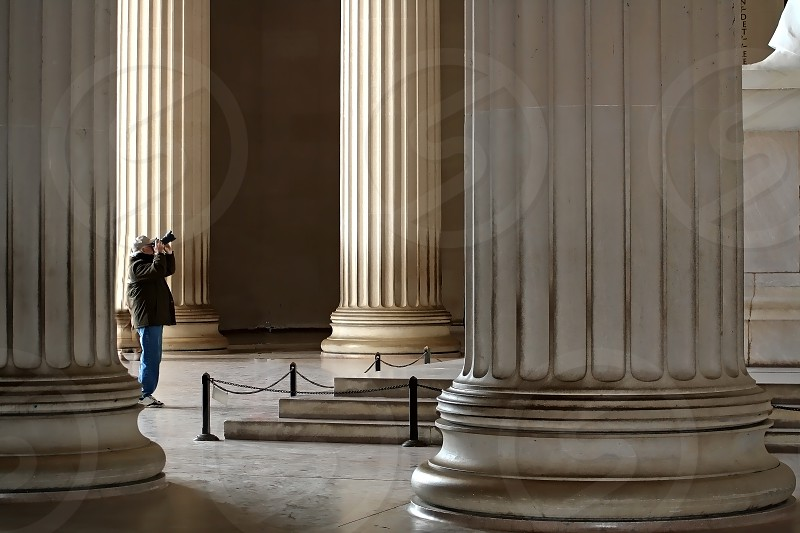 A photographer is dwarfed by huge white columns as he stands between them taking a picture of Abraham Lincoln in the Lincoln Memorial. photo