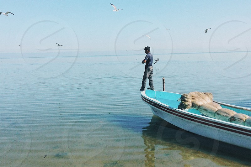 man on edge of teal and white boat photo