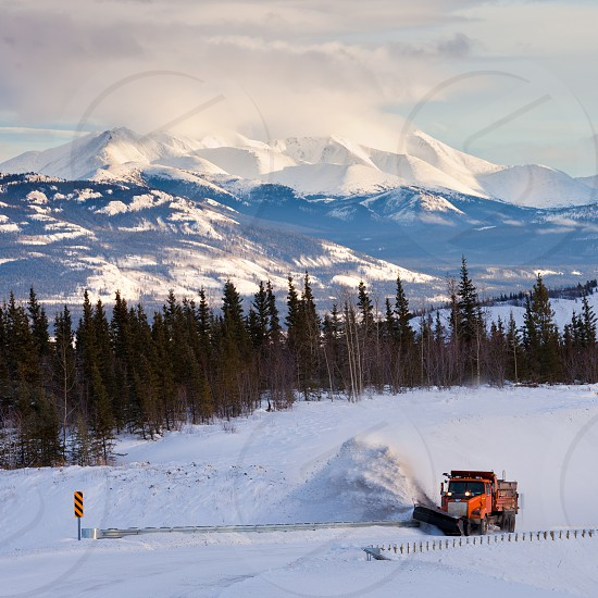 Snow plow clearing road after snow storm blizzard in beautiful rural cold winter landscape of Yukon Territory Canada photo