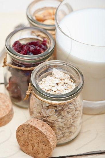healthy breakfast ingredients milk oat cashew nuts dried cramberry craisinns photo