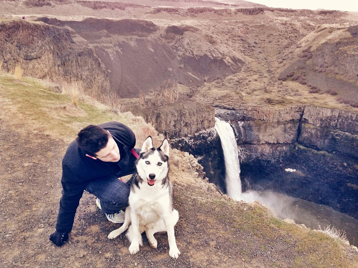 dog and man sitting on cliff photo