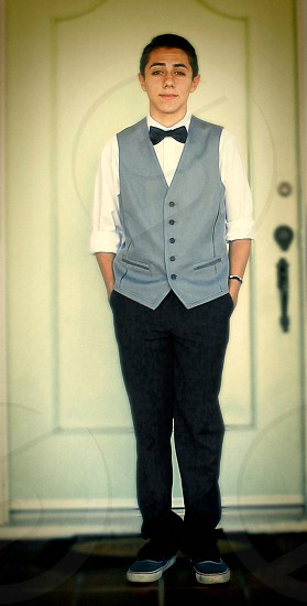Teen wearing a vest white shirt and bow tie photo