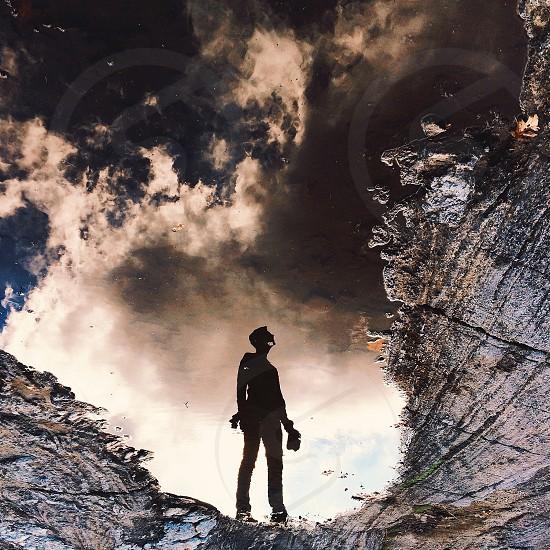 man silhouette standing facing grey mountain photo