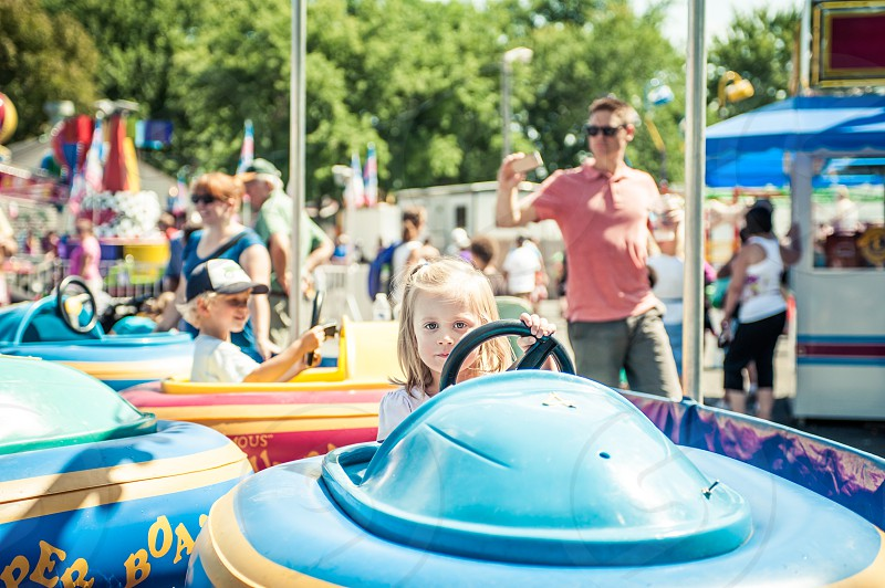 kids children bumper boats fair carnival fun boat steering girl female blonde amusement park happy summer warm hot pool water festival ride riding driving smile smiling blue colorful photo