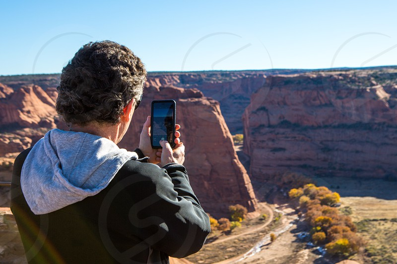 Thanksgiving vacation man taking a cell phone picture over canyon de chelly national park Arizona photo
