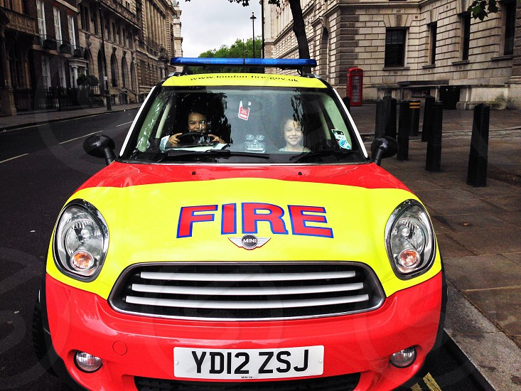 red and yellow fire mini cooper with two smiling kids in front seat parked on side of road photo