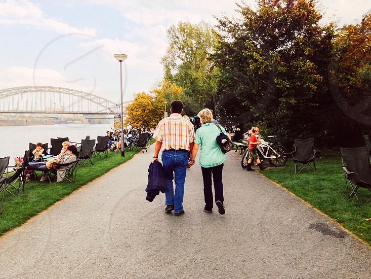 couple walking on asphalt pathway photo