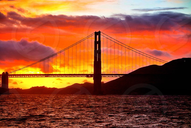 Golden Gate bridge suspension sunset night cloudy stormy San Francisco Bay Area Northern California colorful peaceful waves ocean icon tourist attraction  photo