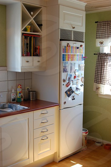 kitchen area with refrigerator and wooden drawers photo