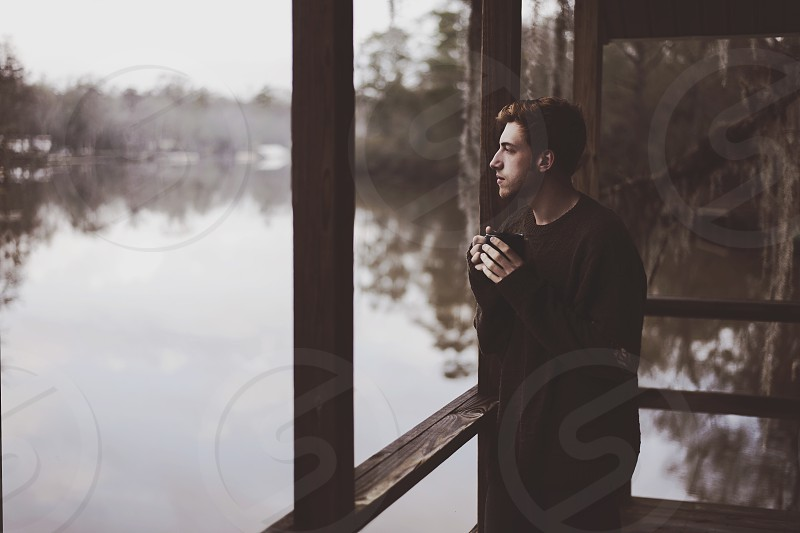 man in black long sleeved round neck shirt standing beside wooden railings photo