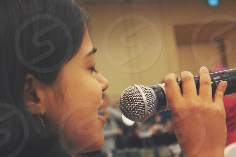 woman singing and holding microphone photo