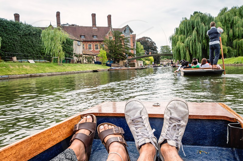 Man and woman feet on a boat punting in the river in  Cambridge. Focus on feet. photo
