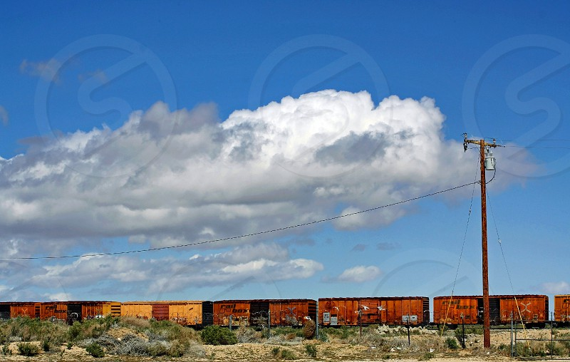 Line of railroad train freight cars against a blue sky photo