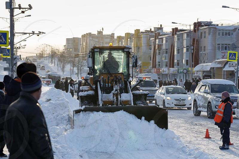 PETROPAVLOVSK KAMCHATSKY CITY KAMCHATKA PENINSULA RUSSIAN FAR EAST - DEC 27 2017: Front end wheel loader cleans after winter snowstorm (blizzards) main road in Petropavlovsk City (sun back light). photo