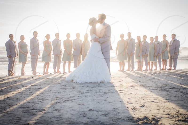newlywed couple kissing in front of witnesses in beach photo