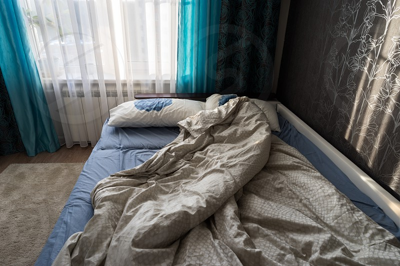 Unmade bed in bedroom photo