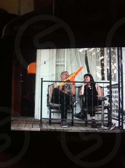 man holding nerf gun next to woman on porch photo