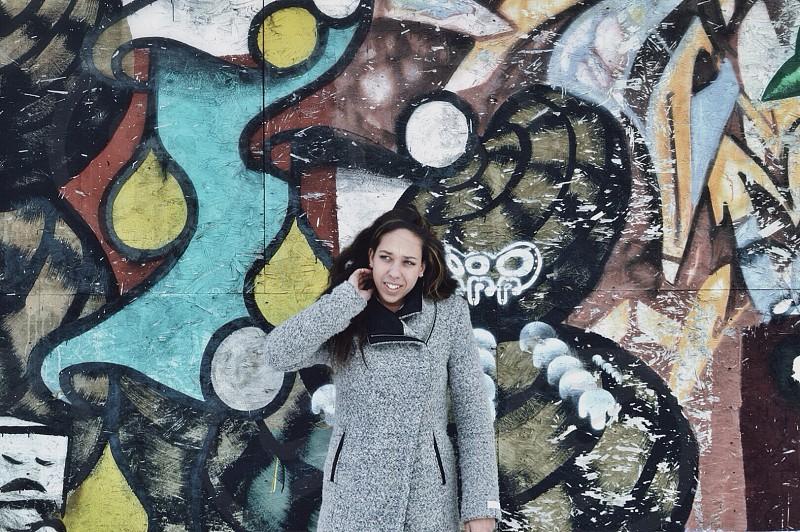 woman in space dye gray coat beside mural photo