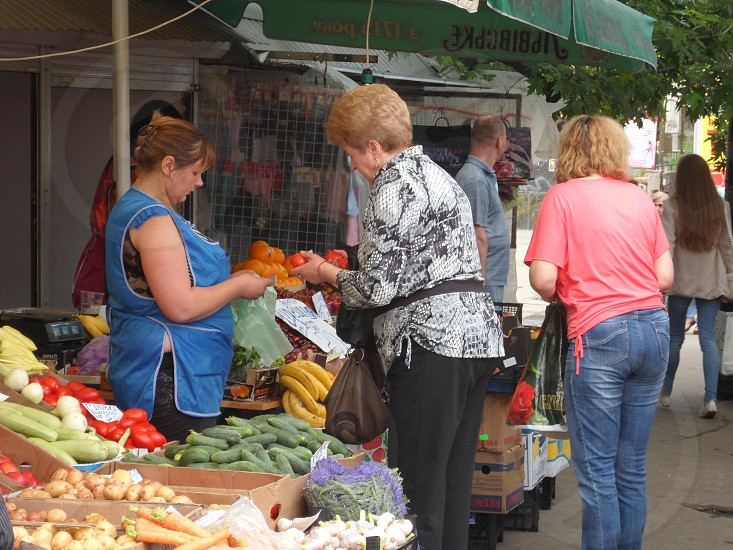 people buying fruits from vendor during daytime photo