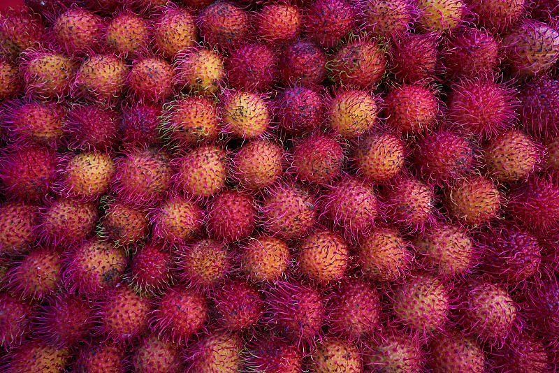 Mexican Rambutan stacked in raws on market photo