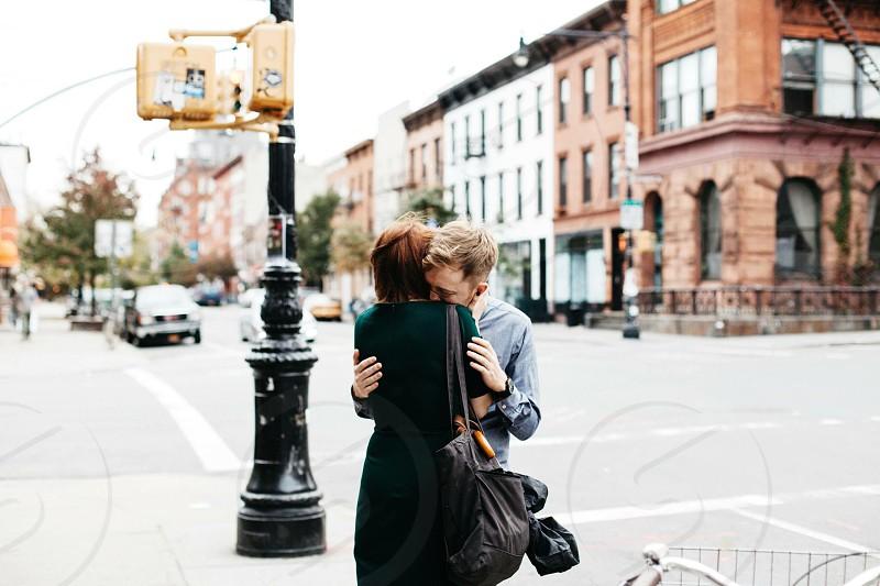 hugging couple on sidewalk during daytime photo