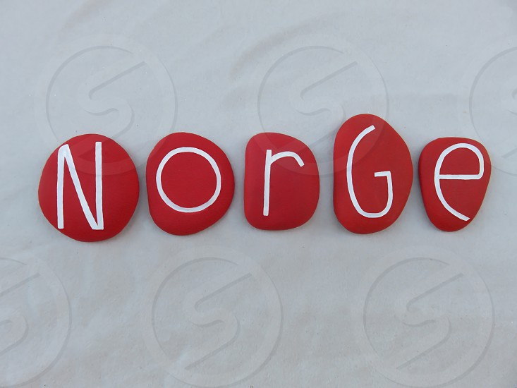Norge norwegian name of Norway scandinavian country composed with red colored and carved stones over white sand                      photo