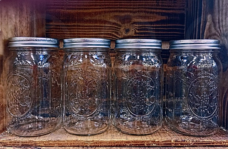 Four empty mason jars stand inside a wooden box photo