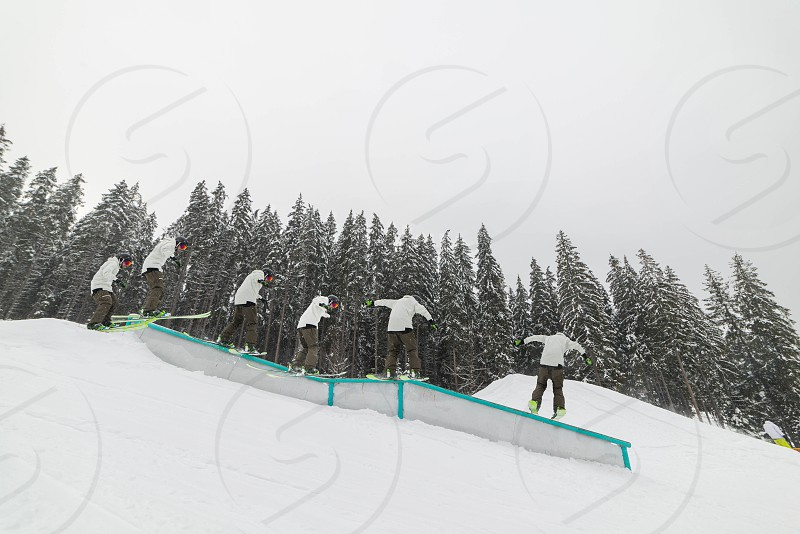 The skier performs a trick on a ramp snowpark in the snowy mountains photo