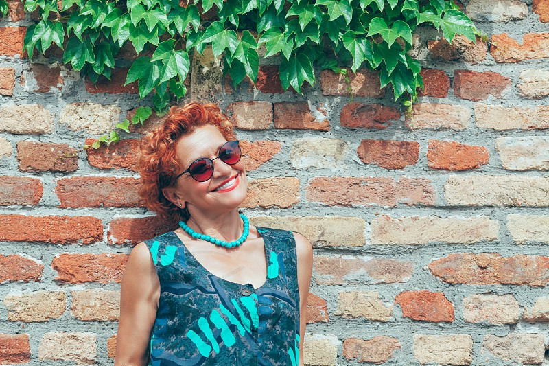 Beautiful retro older woman in front of the brick wall photo