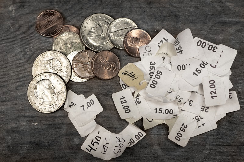 Coins change and price stickers on a wooden table photo
