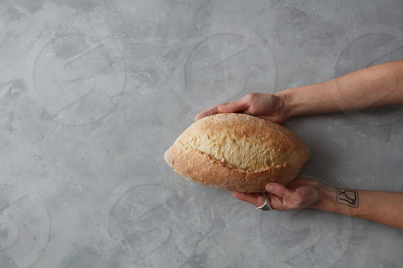 Baker man holding rustic organic loaf of bread in hands photo