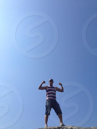 Man shorts denim climbing flexing clear blue sky sunny  photo