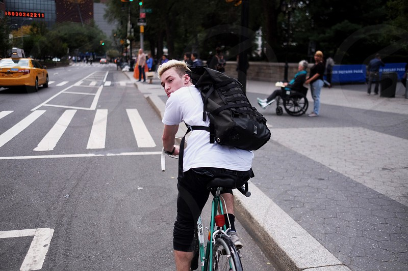 man in white t shirt and black shorts riding green bicycle photo