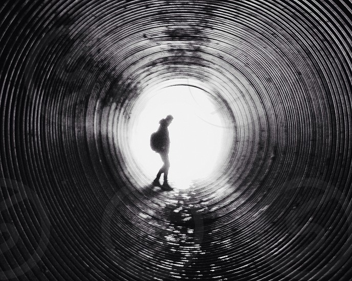 silhouette of person standing at the end of the tunnel in grayscale photo