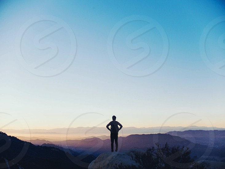 person standing on mountaintop at sunrise photo