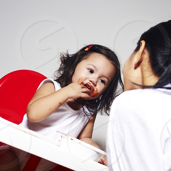 Little baby girl sitting in a baby chair being fed by her mother and making a mess. Her face is covered in yummy chocolate photo
