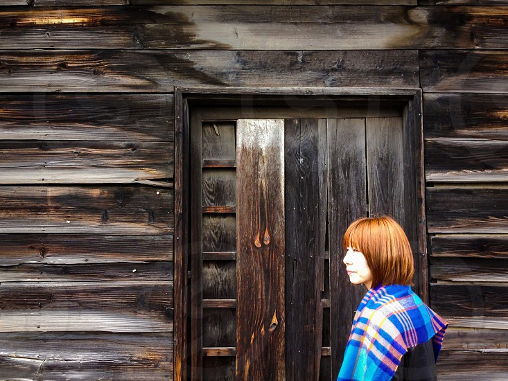 woman in white blue and pink plaid scarf beside brown wooden house photo