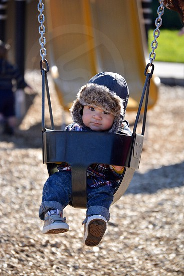 selective focus photo of boy in blue denim pants and plaid tops with hoodie on black swing chair during daytime photo