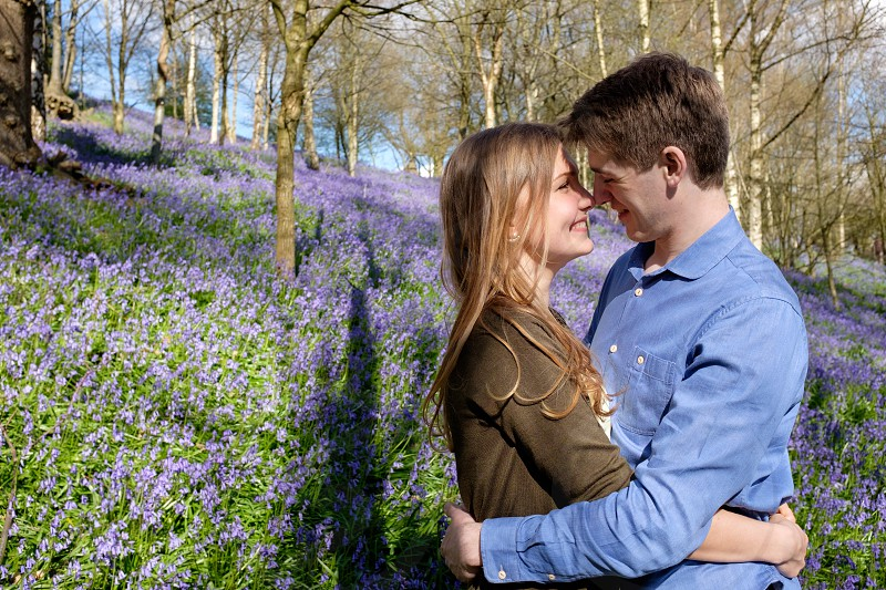 Couple cuddling in the woods nose to nose in the spring  with purple blue bell flowers she is wearing a brown cardigan and he is wearing a blue shirt. The photo is taken in a landscape composition with copy space around the couple. photo