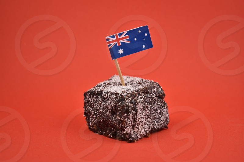 Lamington images. Lamington on a red background. Australian sweet delicacy. Important day. Lamington Day background. Australian cake with flag photo