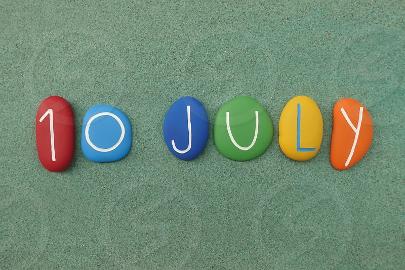 10 July calendar date composed with multi colored stones over green sand photo