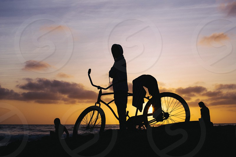 woman beside a bicycle silhouette photo